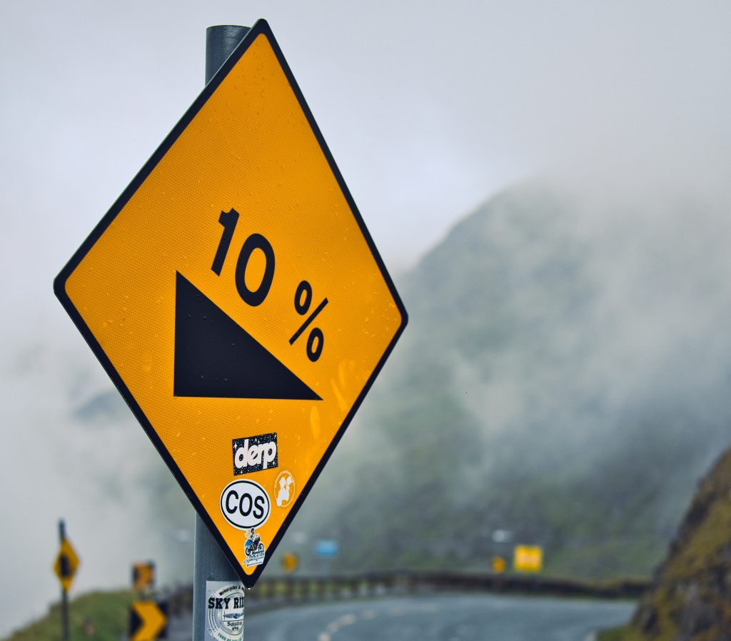 A 10 percent grade sign along a misty mountain road