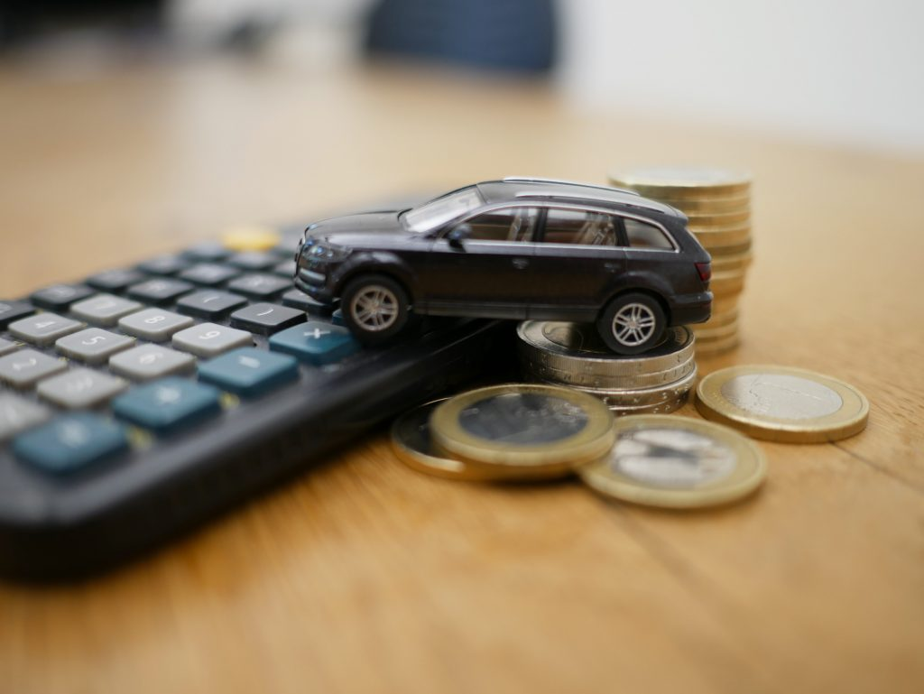 Toy car sitting on change and calculator