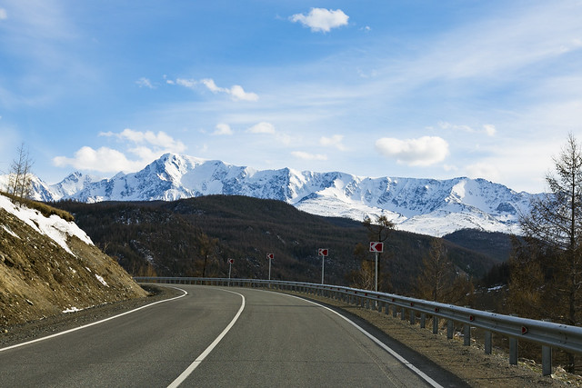 Curved Road with snowy background mountains