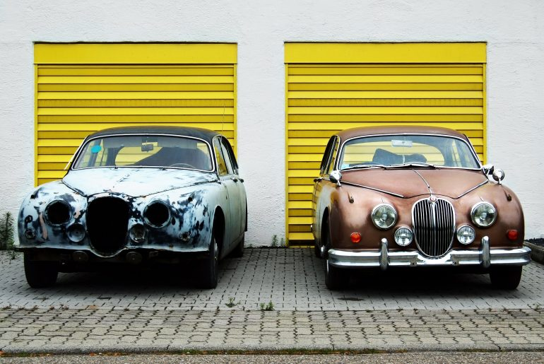 Two old cars side by side in front of yellow garage