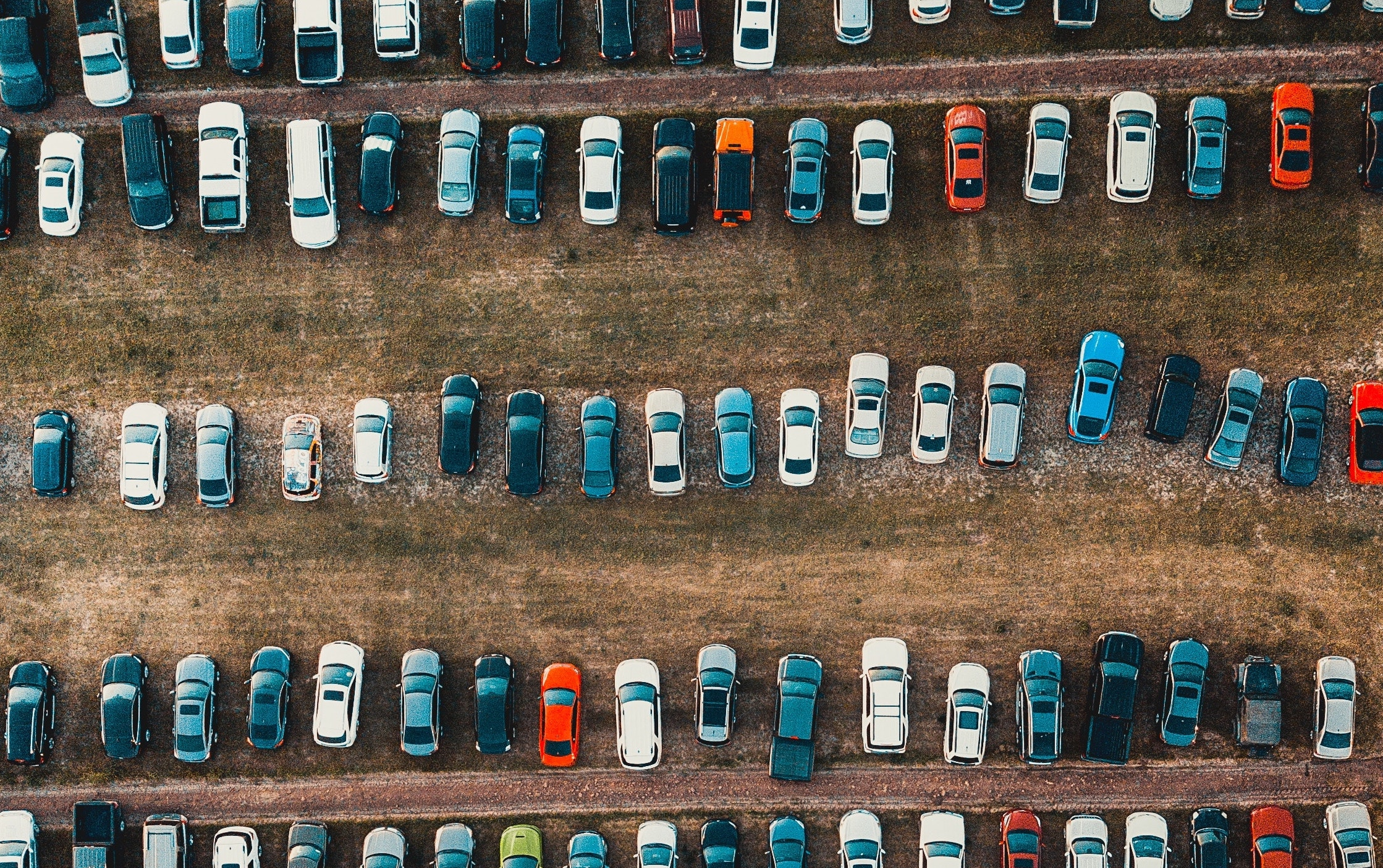 Overhead view of multicolored cars parked in field