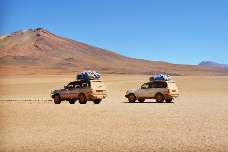 Two Toyota land cruisers in the desert
