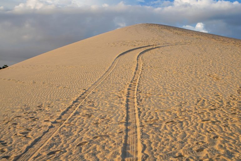 Tire tracks leading up a sand dune