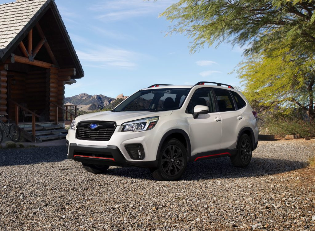 White 2019 Forester Sport parked outside of log cabin