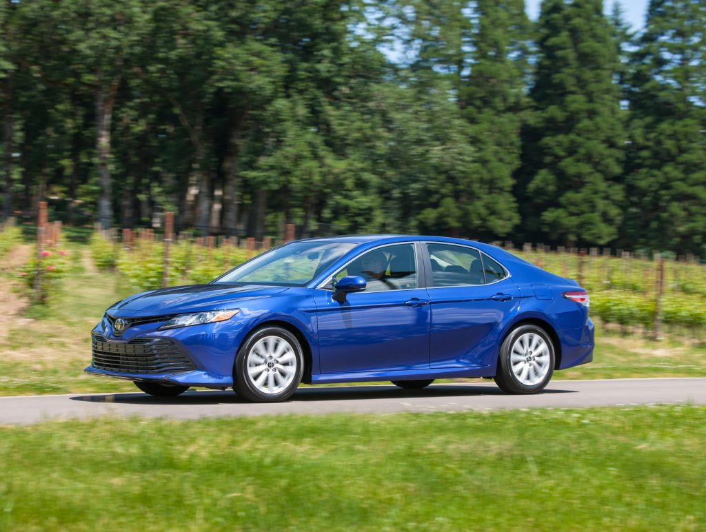 Blue 2018 Toyota Camry LE driving in countryside